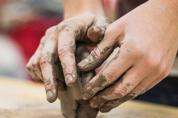 A pair of hands kneads a block of clay
