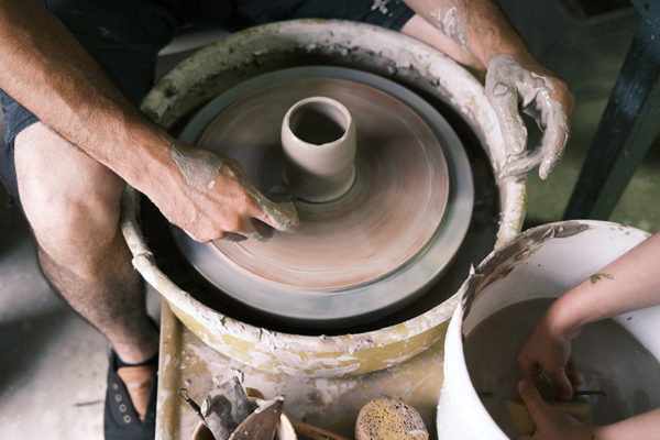 An adult throws a pot on a wheel while a child cleans a sponge