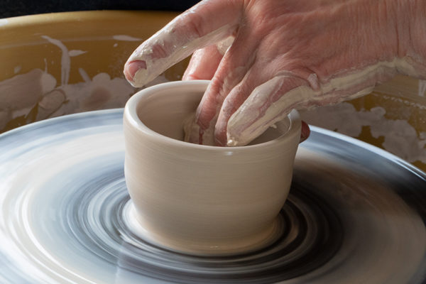 Hands throwing a clay pot on a wheel