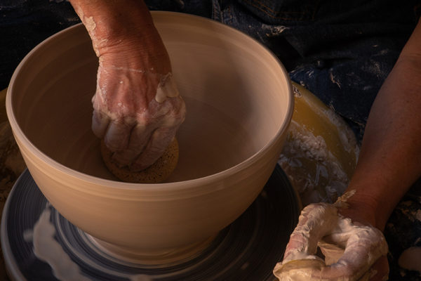 Hands throwing a large pot on the wheel.